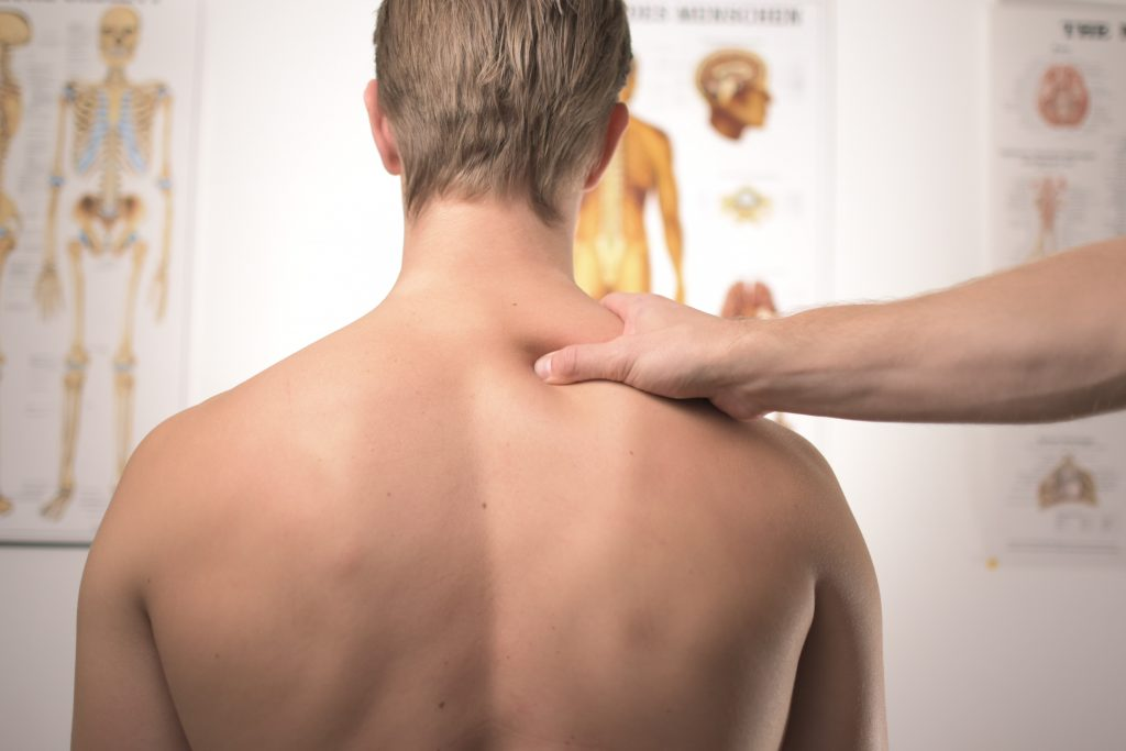 A physiotherapy visit with the physio using his fingers on pressure point on a patient shoulder.